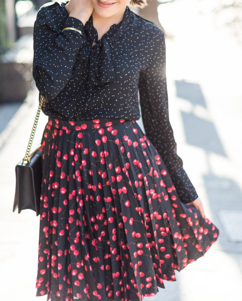 Lifestyle and corporate blogger Amanda Warsavsky wearing a J. Crew cherry skirt and a Banana Republic black bow blouse and Gucci bag