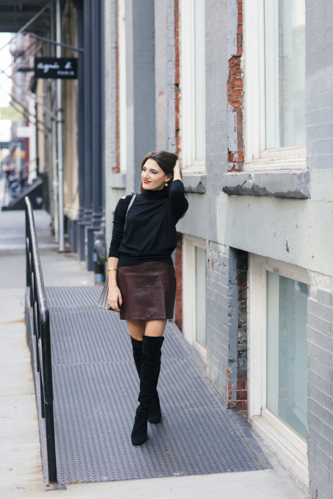Lifestyle and Corporate blogger Amanda Warsavsky wearing a leather skirt, cold shoulder sweater, and over-the-knee boots