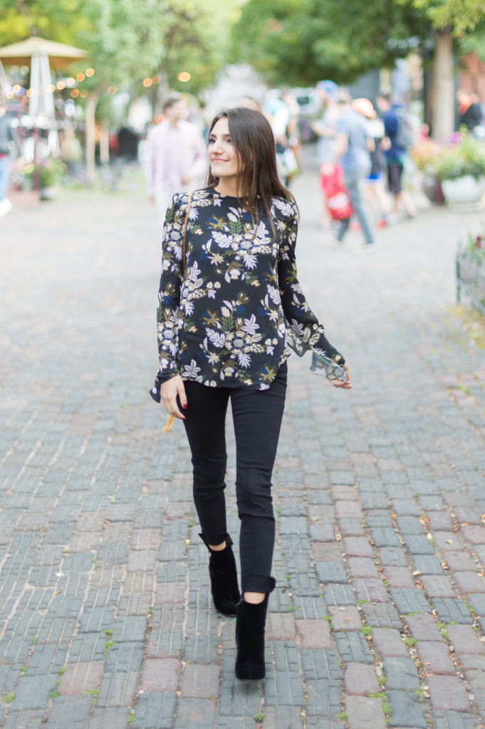 Lifestyle and corporate bogger Amanda Warsavsky wearing black Frame jeans, an A.L.C. ruffle top, and black velvet boots