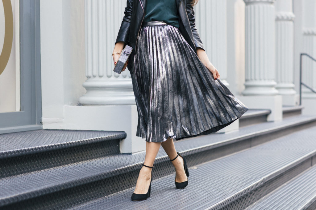 Lifestyle and corporate fashion blogger Amanda Warsavsky wearing a silver pleated skirt and black leather jacket for holiday inspiration