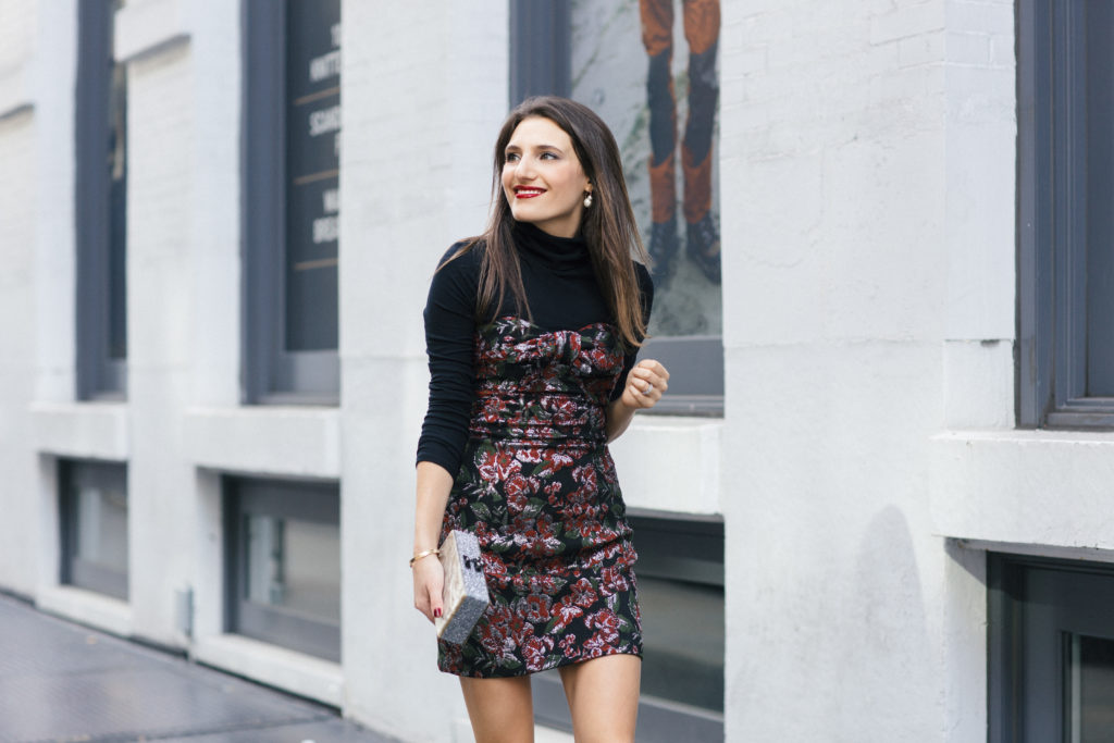 Lifestyle and Corporate Blogger Amanda Warsavsky wearing a strapless holiday dress, black turtleneck and Edie Parker glitter bag