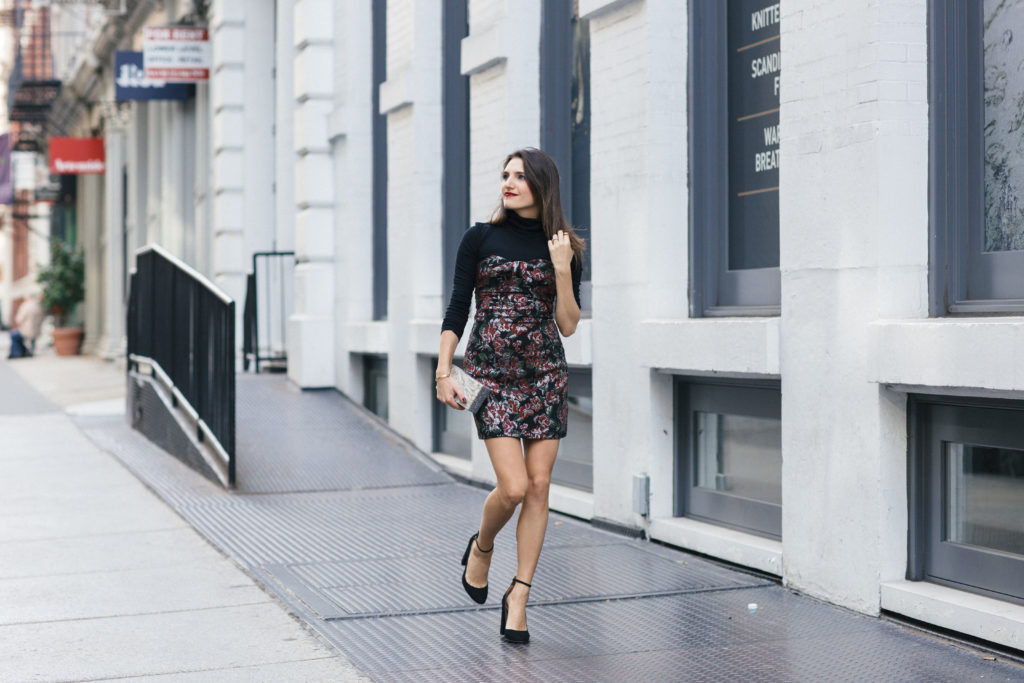 Lifestyle and Corporate Blogger Amanda Warsavsky wearing a strapless holiday dress, black turtleneck, black pumps with an ankle strap and Edie Parker glitter bag