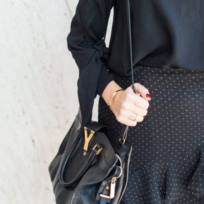 Lifestyle and workwear blogger That Pencil Skirt wearing a Club Monaco black ruffle skirt and a black turtleneck with a black off the shoulder top layered over. With a Saint Laurent bag.