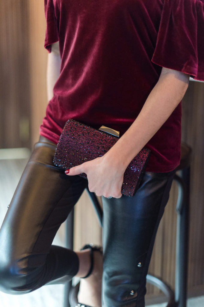 That Pencil Skirt, a lifestyle and work style blogger, wearing vegan leather pants, a burgundy velvet off the shoulder top and a burgundy rhinestone clutch from the White House Black Market holiday collection