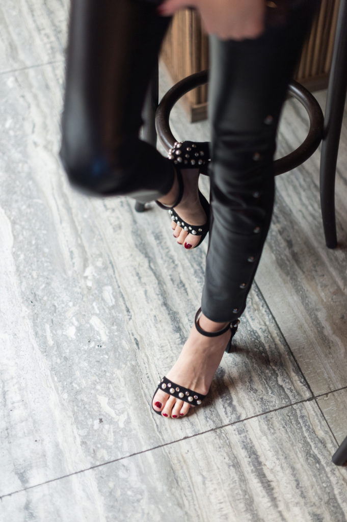 That Pencil Skirt, a lifestyle and work style blogger, wearing vegan leather pants, and pearl embellished black suede sandals from the White House Black Market holiday collection