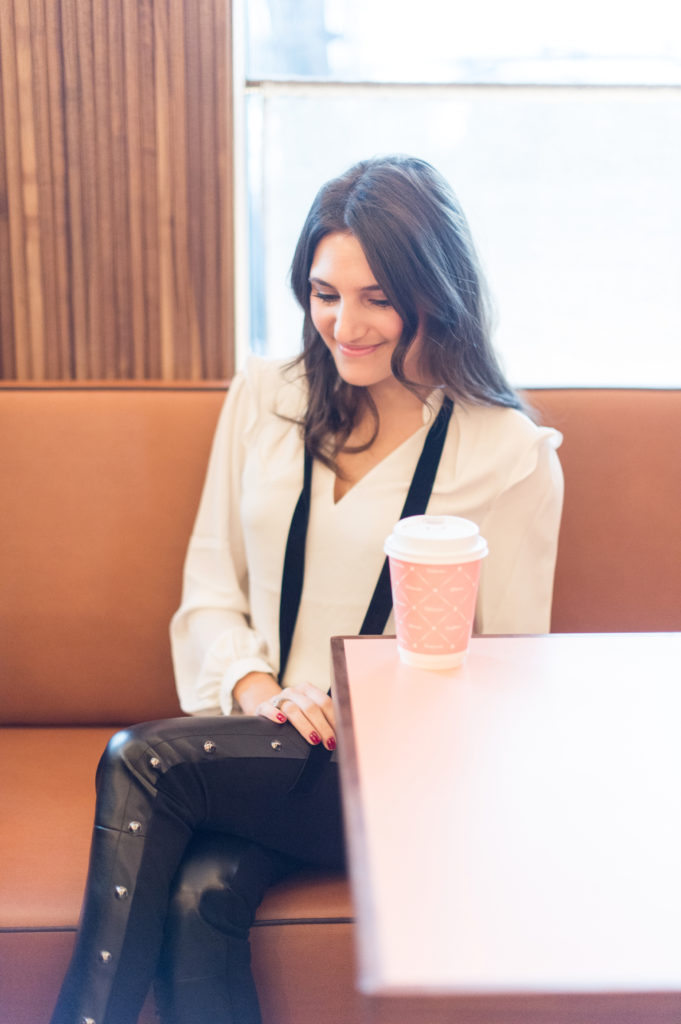 That Pencil Skirt, a lifestyle and work style blogger, wearing vegan leather pants, and a white blouse with a black velvet tie from thefrom the White House Black Market holiday collection