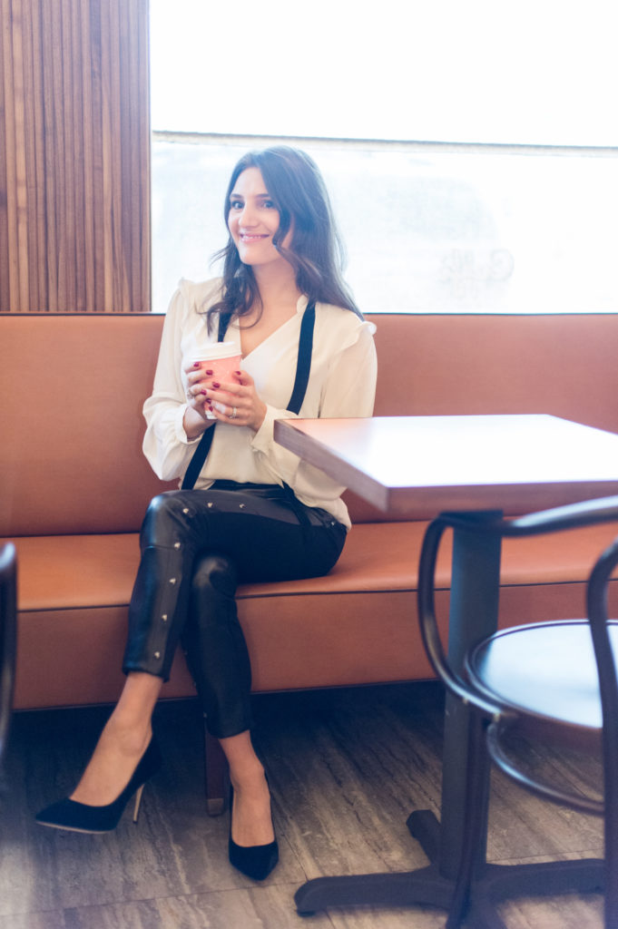 That Pencil Skirt, a lifestyle and work style blogger, wearing vegan leather pants, and a white blouse with a black velvet tie and black velvet pumps from the White House Black Market holiday collection