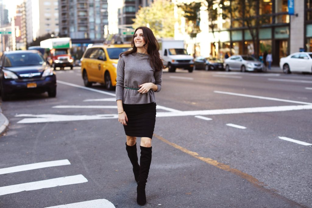 That Pencil Skirt, a lifestyle and work wear blogger wearing an MM.LaFleur Kendall sweater with a thin green belt and a black stretchy ruched skirt