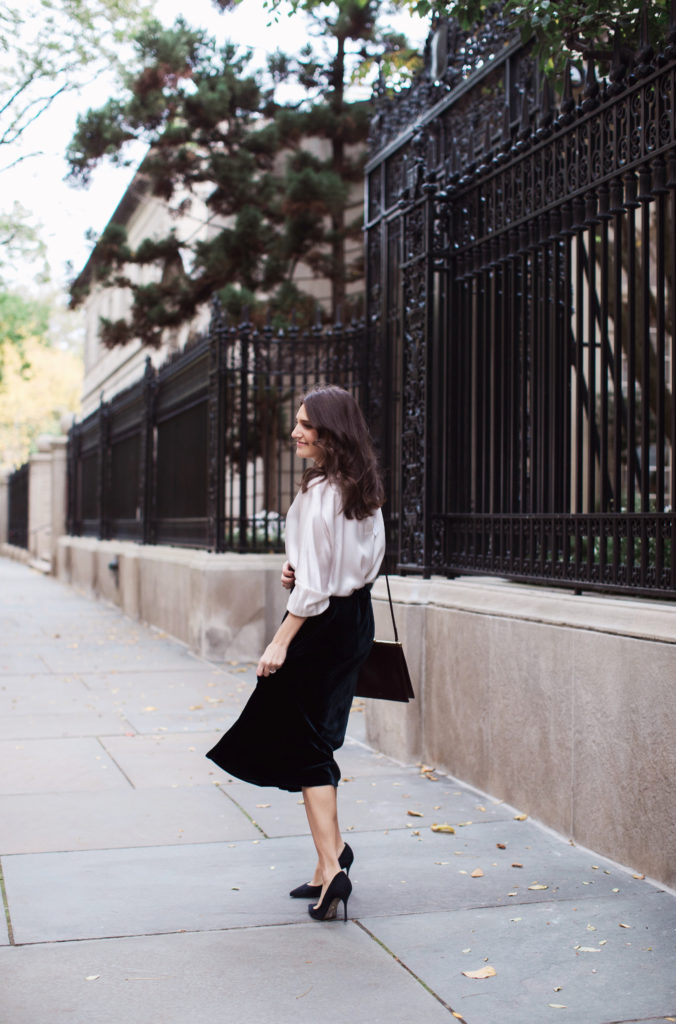That Pencil Skirt, a lifestyle and workwear blogger wearing a Vince Velvet midi skirt with a Vince silk silver blouse and navy suede pumps