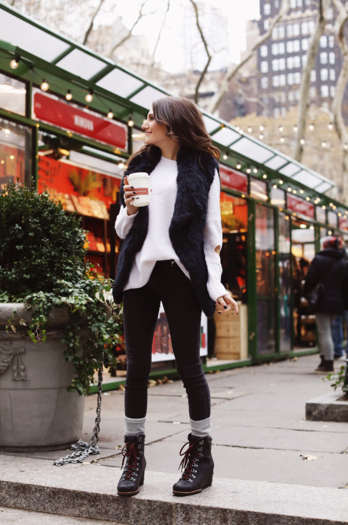 Lifeistyle blogger That Pencil Skirt wearing Sorel boots, cashmere socks. a black fur vest and an Aqua sweater all bought at Bloomingdales