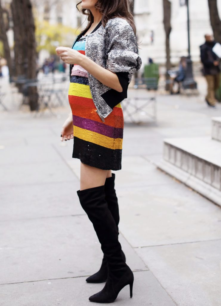 That Pencil Skirt, a fashion blogger, wearing an Alice and Olivia striped sequin color mini dress, with a Philip Lim silver embroidered bomber jacket and over the knee black suede boots